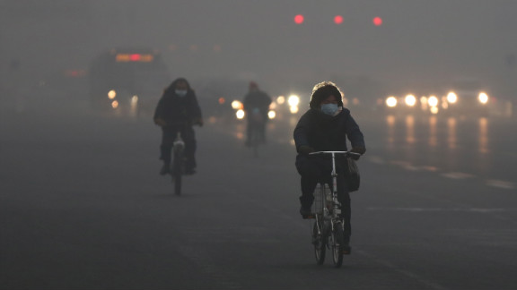 Beijing residents wear masks as they ride through the pollution on January 29.