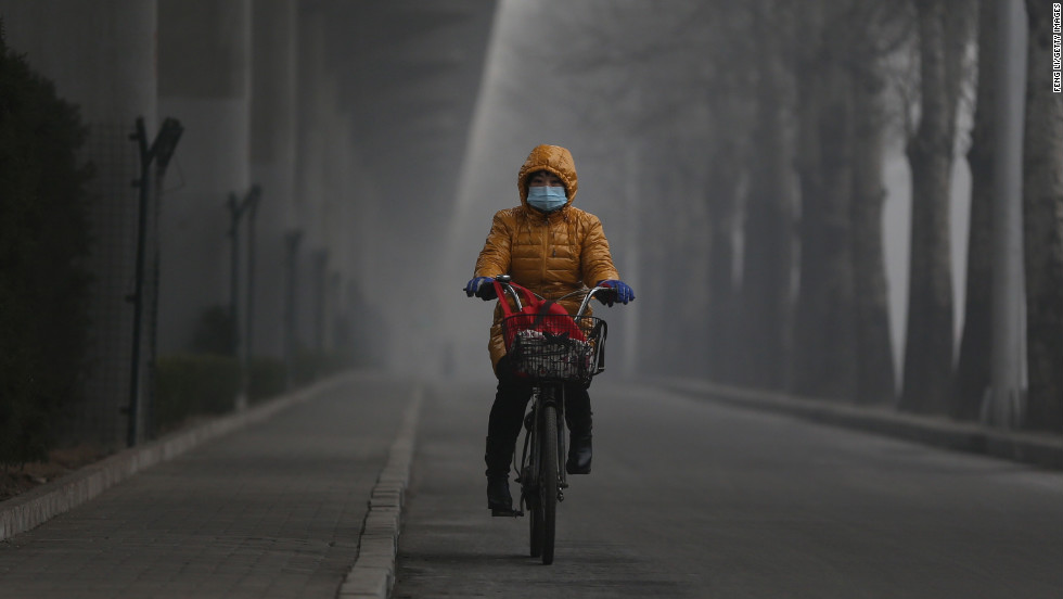 A woman wears a mask and rides her bike on January 23.