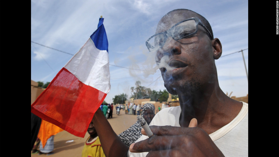 A man waves a French flag as residents celebrate the arrival of Niger troops on January 29 in Ansongo.