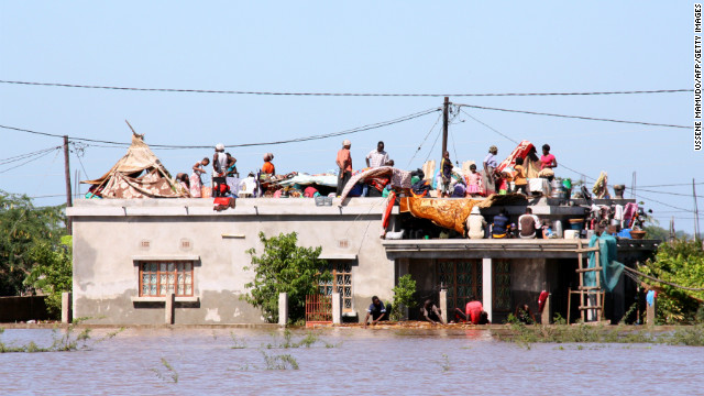 Residents flee to the roof of a house in Mozambique on Friday to escape the floods.