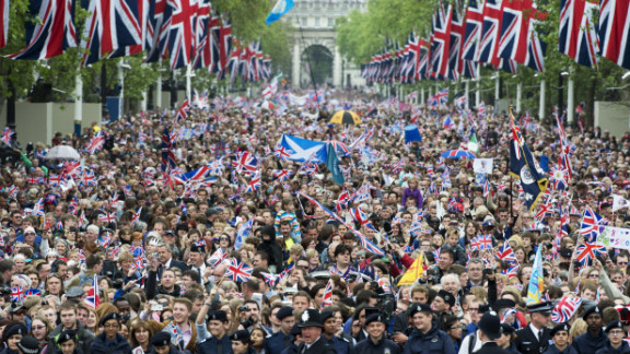 Crowds cheer and wave Union Jacks as they march down the Mall toward Buckingham Palace to celebrate the Queen