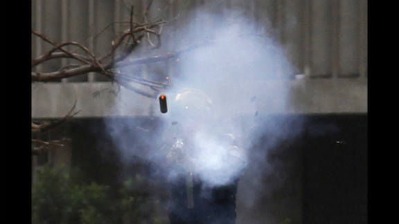 A police officer fires a tear gas canister during clashes with protesters near Tahrir Square on January 30.