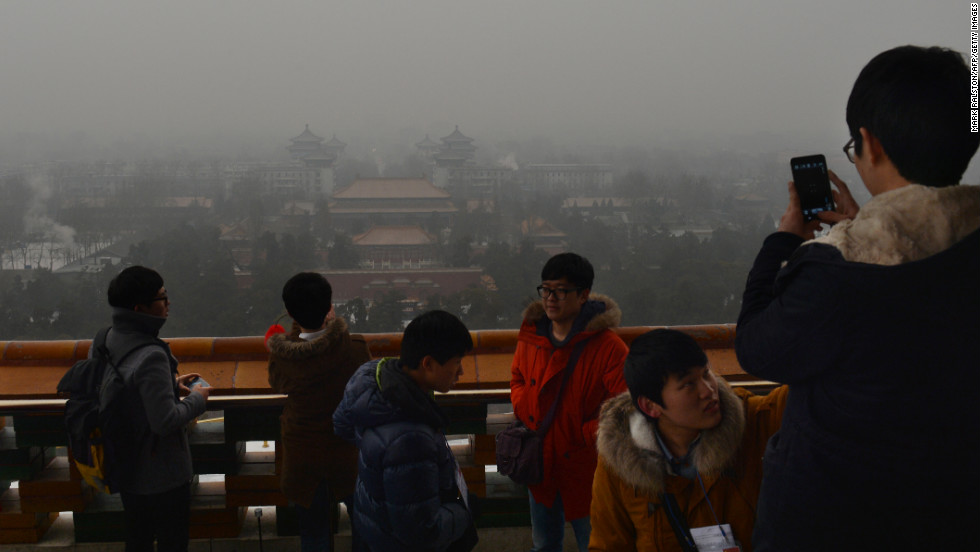 Japanese tourists take photos from Jingshan Park as smog continues to shroud Beijing on January 31. The smog also forced the cancellation of airline flights and highway closures in parts of Beijing, Chinese state media reported.
