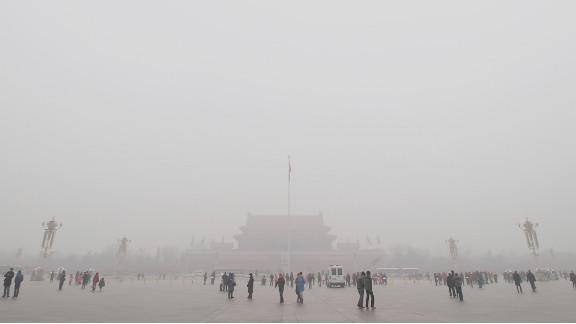 Tourists visit smog-shrouded Tiananmen Square.