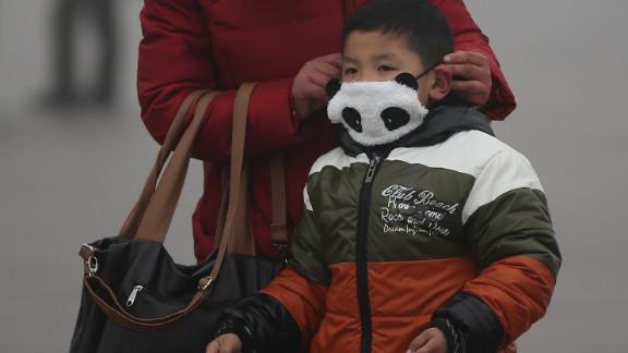 A small child wears a panda mask at Tiananmen Square.