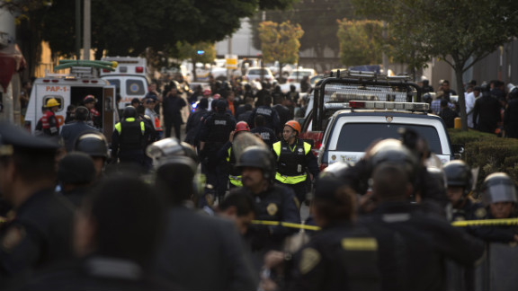 Police officers and rescue workers respond to the headquarters of state-owned Mexican oil giant Pemex in Mexico City where a blast killed at least 30 and injured more than 100 on Thursday, January 31.