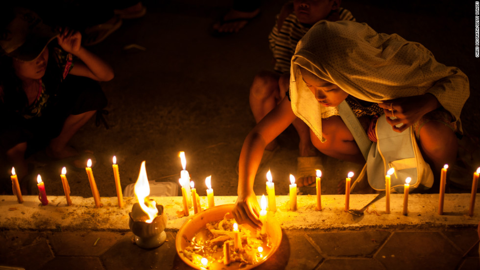 Young children light candles outside the Royal Palace on Thursday, ahead of a lavish funeral procession that saw his body carried from the palace to a funeral pyre in a nearby park.