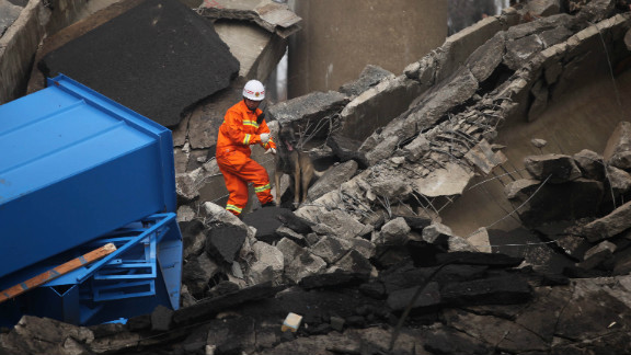 A rescuer looks for survivors at the scene near the city of Sanmenxia, Henan province, on February 1, 2013.