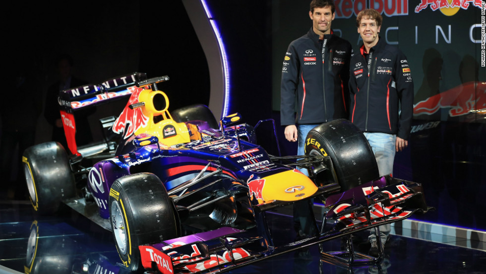 Mark Webber, left, and triple world champion Sebastian Vettel pose with the Red Bull they will be driving this year.