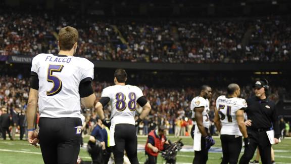 Quarterback Joe Flacco and Baltimore Ravens teammates wait on the field as a third-quarter power outage brings Super Bowl XLVII to a temporary halt.