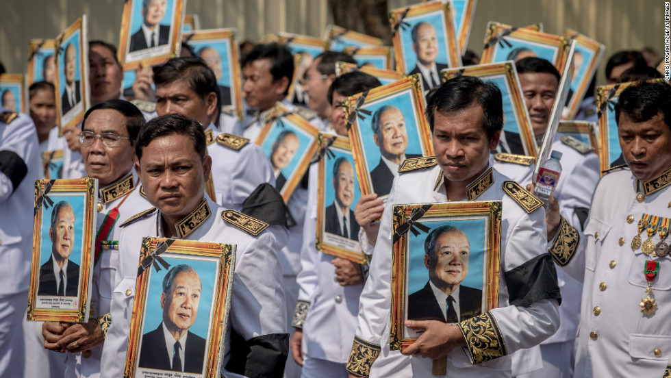 Mourners carry portraits of former King Norodom Sihanouk during the funeral procession on Friday in Phnom Penh.