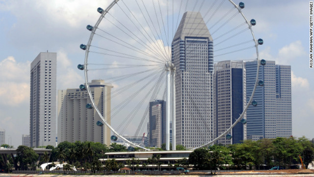In this picture taken on April 15, 2008, the 165 meter high Singapore flyer stands against a panorama of highrise buildings in Singapore. Officials in Singapore have changed the direction of the world's biggest observation wheel because feng shui masters said it was taking good fortune away from the city, a report said August 9. 2008. The Singapore Flyer, which opened earlier this year, had originally revolved so that it rose to face the business district and went down overlooking the sea, the Strait Times newspaper said. AFP PHOTO/ROSLAN RAHMAN (Photo credit should read ROSLAN RAHMAN/AFP/Getty Images)