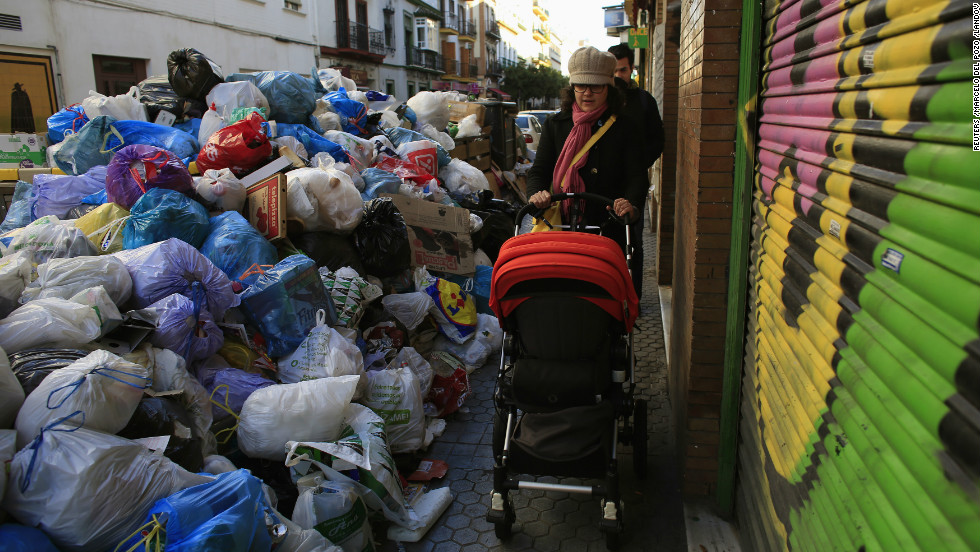 A woman pushes her baby through the trash-choked streets on February 5.
