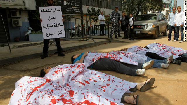 Activists participating in a flash mob don bloodied sheets as they lie in the streets outside the Ministry of Labour in Beirut to protest over violence against migrant workers in April 2012.
