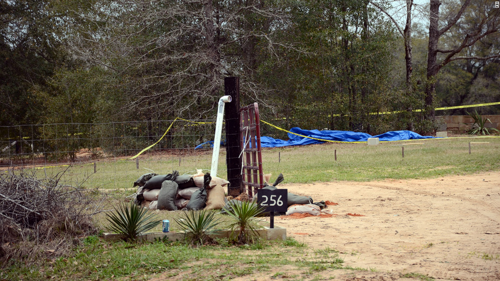 A white PVC pipe used by FBI agents and Dale County, Alabama, negotiators to communicate with Dykes protrudes out of the ground on Monday, February 4. For almost a week, Dykes held a 5-year-old boy hostage in a bunker after taking the boy from his school bus and killing its driver.
