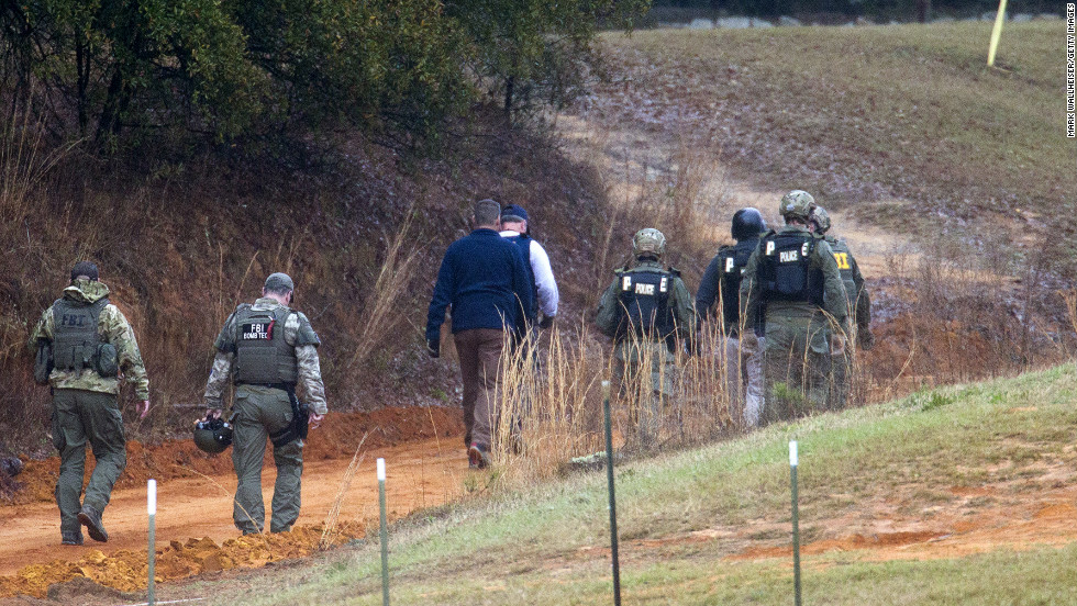 Law enforcement officers walk down a dirt road to the bunker to process the crime scene on Tuesday, February 5, after the standoff ended.