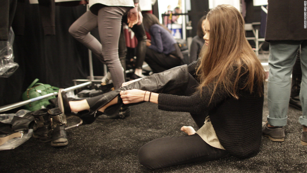 A model adjusts her outfit backstage on February 6.