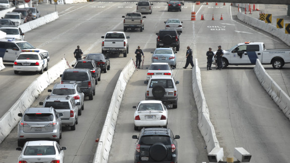 Department of Homeland Security officers search vehicles at the San Ysidro Port of Entry in San Diego on February 7 as they search for former LAPD officer Christopher Dorner.
