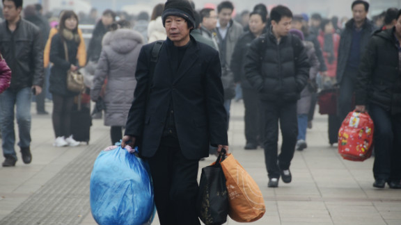 A man prepares to take the train at the entrance of Beijing Railway Station on January 28.