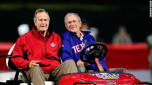 President George H.W. Bush, left, and his son President George W. Bush appear at a World Series game in October 2010.