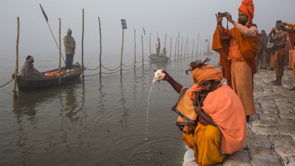 A Sadhu pours water from a conch shell as he prays on the banks of the Ganges river.