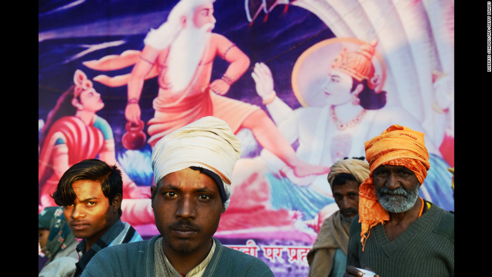 Indian devotees stand in front of a painting depicting Hindu gods during the Maha Kumbh Mela festival on February 8.