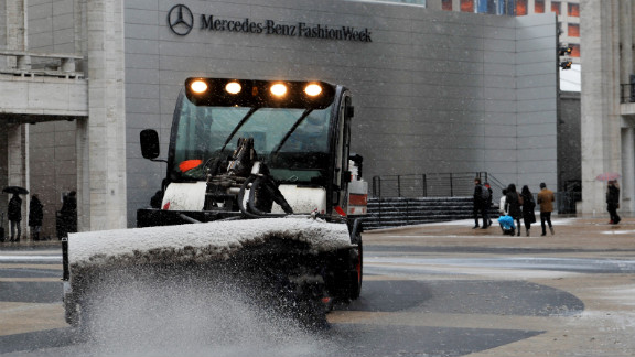 A sweeper clears snow in front of the Mercedes-Benz Fashion Week tents on February 8 at Lincoln Center in New York.