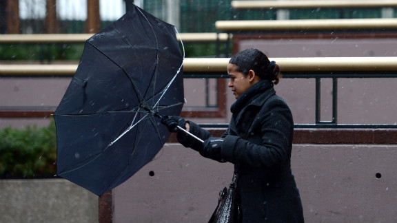 A woman tries to right her umbrella while dealing with wind and precipitation in New York on February 8.