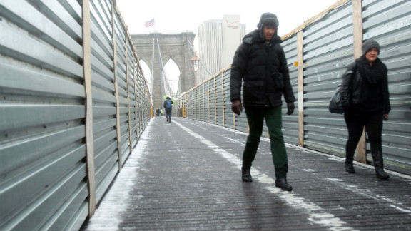 Two people carefully walk across the Brooklyn Bridge in the snow and sleet on February 8.