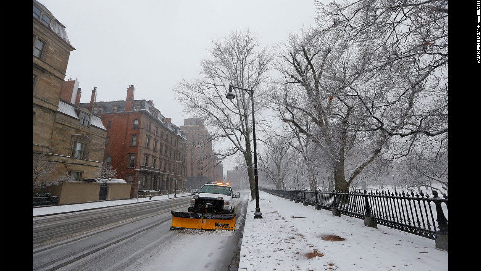 A snowplow sits on the street while snow falls near Boston Common on Friday.