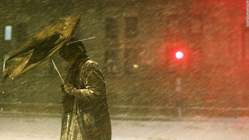 A pedestrian makes his way through driving snow with a broken umbrella in the Back Bay neighborhood on Friday, February 8 in Boston.