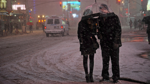 People wait for a taxi in the snow in Times Square.