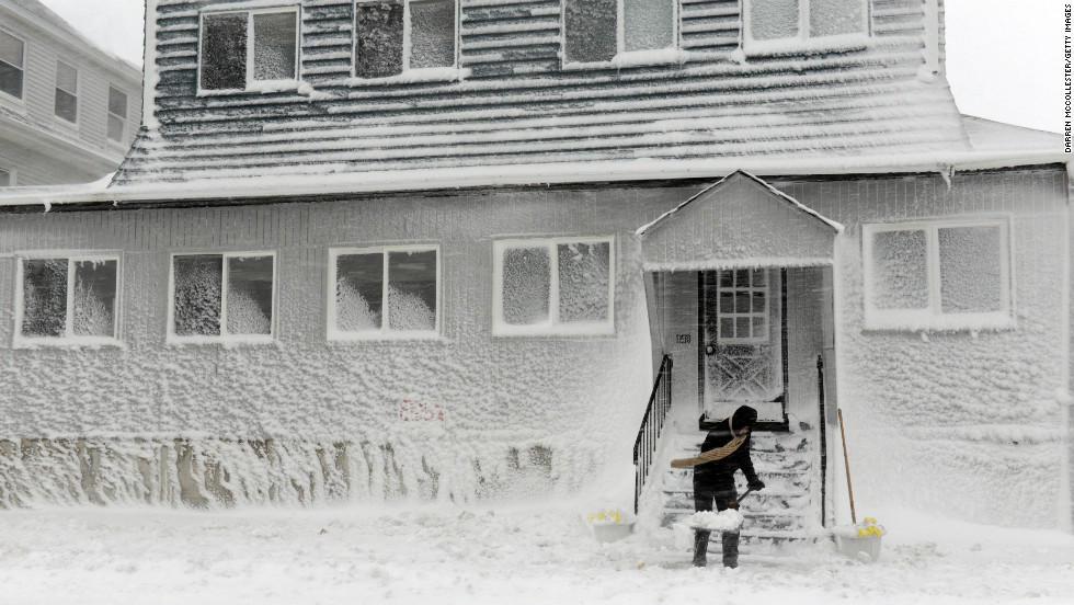 A man shovels snow along Winthrop Shore Drive in Winthrop, Massachusetts.