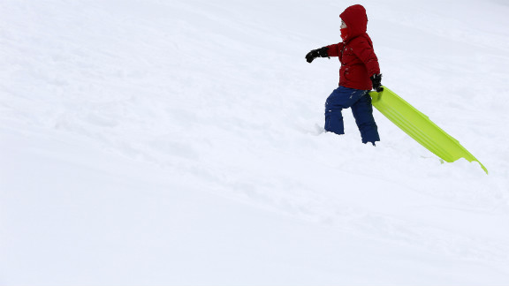A child drags his toboggan up a hill in Central Park.