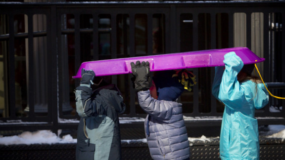 Children carry a sled through the Financial District in New York City on Saturday.