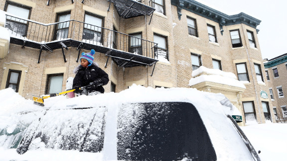 Saniyyah Phillips, 8, scrapes the snow off of the top of her father