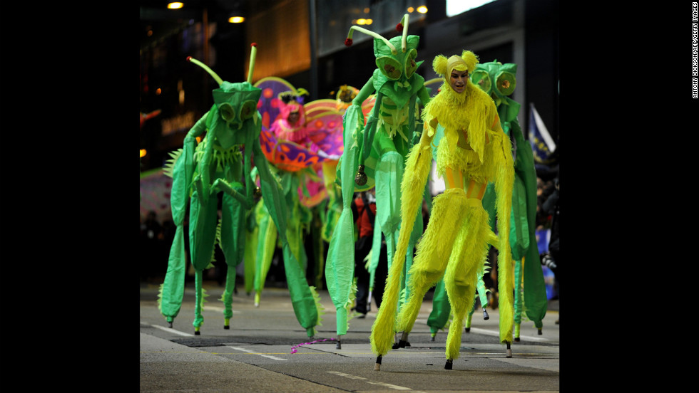 People on stilts and in costume walk down Hong Kong's streets on February 10.
