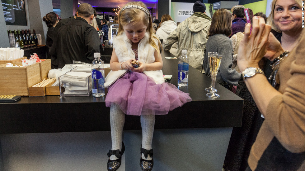 A young girl eats the free energy bar she got in the lobby during New York Fashion Week on Sunday, February 10.