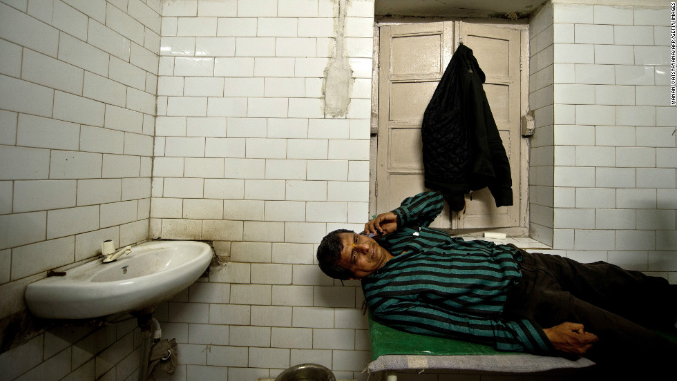 Rajesh, 45, talks on his mobile phone as he lies on a bed after being injured in a stampede that killed at least 10 people at the main railway station serving India's giant Kumbh Mela festival.