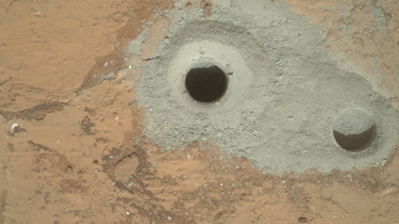 "The rover drilled this hole, in a rock that's part of a flat outcrop researchers named ""John Klein,"" during its first sample drilling on February 8, 2013."