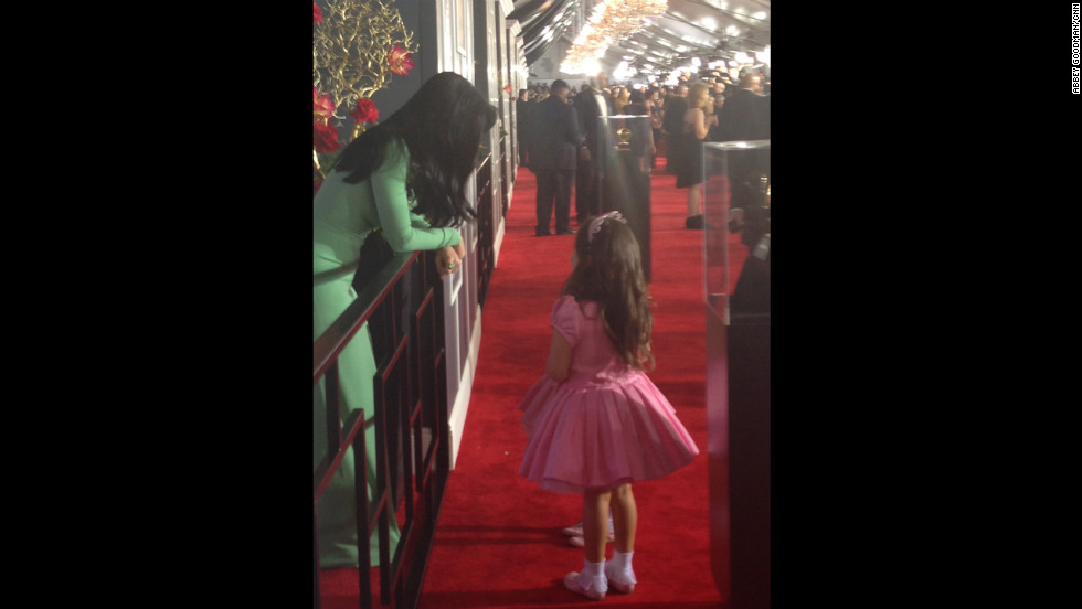 "Katy Perry planned to race past the press like her BFF Rihanna, but couldn't resist stopping for a little girl talk with ""The Ellen Degeneres Show's"" pink princesses Sophia Grace and Rosie (obscured in photo). What do you think they're talking about?"