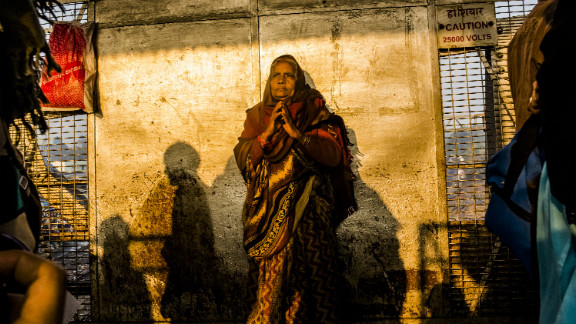 A Hindu devotee waits on February 11 as people move through the site of Sunday's stampede in Allahabad, India. Tens of millions of Hindu pilgrims flock to the banks of the Ganges River for what is thought to be the world's largest religious gathering.