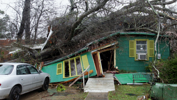 A tree lies atop a house on Monday, February 11, in Hattiesburg, Mississippi, the day after a tornado barreled through the area. At least 15 tornadoes formed across southern Mississippi and Alabama as a cold front moved in Sunday, February 10.