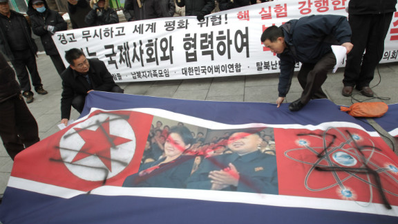 South Korean conservative protesters position a defaced North Korean flag as they participate in a rally demonstrating against North Korea