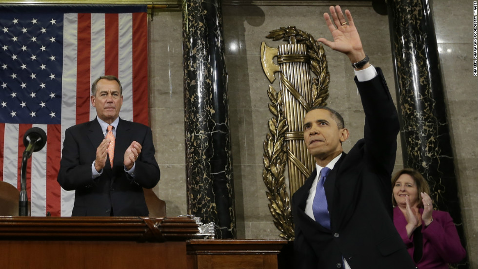 Obama waves after completing his State of the Union address, as House Speaker John Boehner applauds.