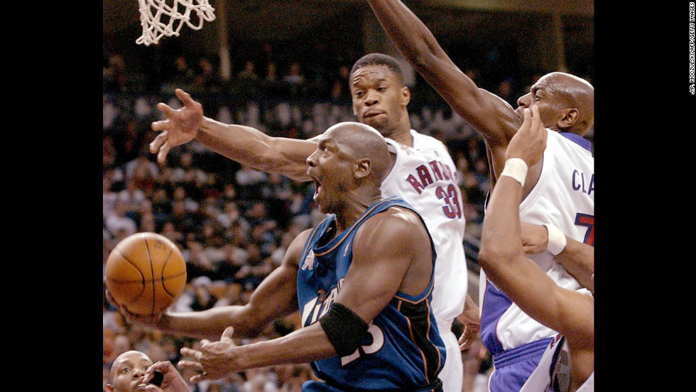 Jordan, playing for the Washington Wizards, drives to the hoop past Toronto Raptors forwards Antonio Davis, center, and Keon Clark, right, in 2002.