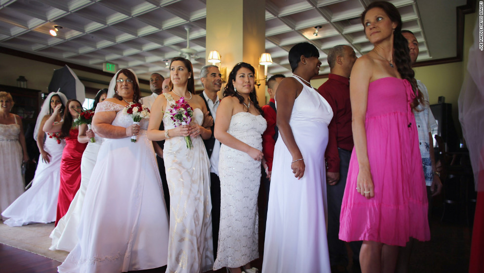 Brides line up with their husbands-to-be during a group Valentine's Day wedding at the National Croquet    Center in West Palm Beach, Florida.