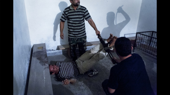 Second prize -- spot news single:  Syrian opposition fighters interrogate captured government informants on July 31, 2012, in Aleppo, Syria, in a photograph by Emin Ozmen. The informants were declared guilty and tortured throughout the night, according to Ozmen.