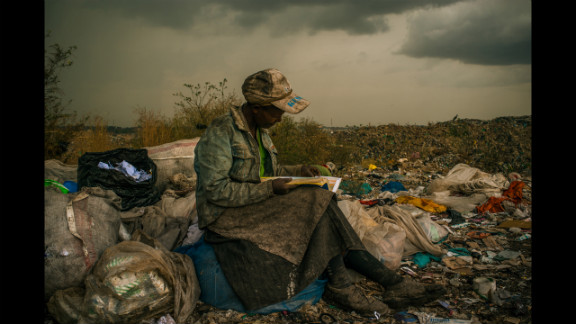 First prize -- contemporary issues single: A woman stops to read a book during her shift picking up trash at a dump near slums in Nairobi, Kenya, on April 3, 2012.