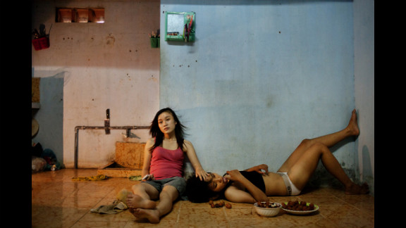First prize -- contemporary issues stories:  Phan Thi Thuy Vy and Dang Thi Bich Bay watch TV after studying on June 22, 2012, in Da Nang, Vietnam. The couple have been together for a year, according to photographer Maika Elan, in a country that